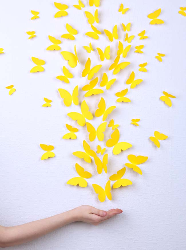 Paper yellow butterflies fly on wall in different directions