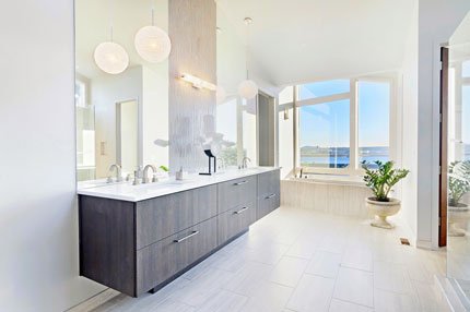White paint and tiles and large mirrors help create an open, light bathroom.